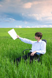 Businessman working on grassland under blue sky. Businessman working on green grassland under blue sky Royalty Free Stock Photo