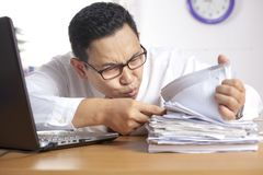 Businessman Working Hard at the Office. Portrait of Asian businessman working hard at the office royalty free stock photography