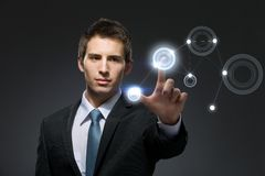 Businessman working with hightech touchscreen. Pressing buttons on it, isolated on black background stock images