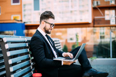 Businessman working with his computer and drinking coffee on a bench outdoors royalty free stock image