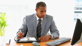 Businessman working at his desk and writing in diary stock video