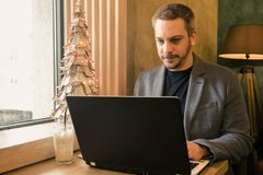Businessman working on his laptop at the cafe. Christmas decoration stock photo
