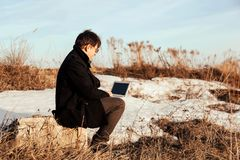 Businessman working with his laptop outside royalty free stock image