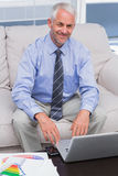 Businessman working with his laptop and smiling at camera Royalty Free Stock Photos