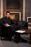 Businessman working at home. Talking on mobile, making notes Stock Photo