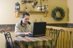 Businessman working from home. On his laptop Stock Images