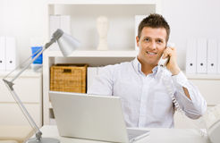 Businessman working at home. Casual businessman working at home using laptop computer, talking on phone Stock Image