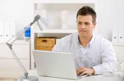 Businessman working at home. Casual young businessman working at home on laptop compuer, looking at screen Stock Image