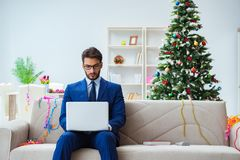 The businessman working at home during christmas. Businessman working at home during christmas Royalty Free Stock Image