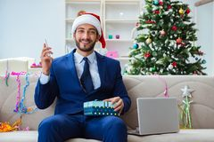 The businessman working at home during christmas. Businessman working at home during christmas Stock Photos