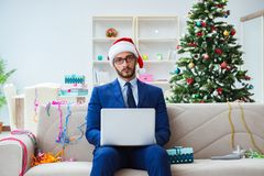 The businessman working at home during christmas. Businessman working at home during christmas Royalty Free Stock Photo