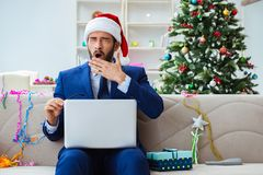 The businessman working at home during christmas. Businessman working at home during christmas Royalty Free Stock Photography