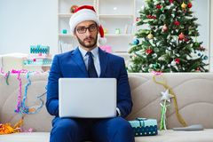 The businessman working at home during christmas. Businessman working at home during christmas Stock Photo