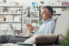 Businessman working at home. Confident businessman working at home, he is sitting on the sofa with a laptop on his lap and using a smartphone Royalty Free Stock Photography