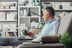 Businessman working at home. Confident businessman working at home, he is sitting on the sofa with a laptop on his lap and using a smartphone Stock Photo