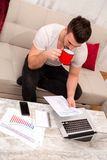 Businessman working at home meanwhile drinking coffee Stock Image