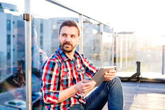 Businessman working from home on tablet, sitting on balcony. Young businessman in checked shirt and jeans writing on a tablet, sitting on the balcony Stock Photo