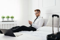 Businessman working from a hotel room with his mobile phone Royalty Free Stock Photography