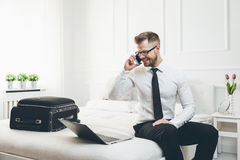 Businessman working from a hotel room with his mobile phone Stock Images