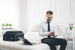 Businessman working from a hotel room with his mobile phone Stock Photography