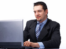 Businessman Working On Laptop. Happy young business man working on a laptop, isolated against white background Royalty Free Stock Images