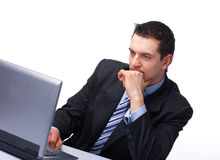 Businessman Working On Laptop. Young business man working on a laptop, isolated against white background Stock Images