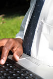 Businessman working on laptop. An african businessman working on laptop outdoors Stock Photography
