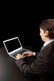 Businessman working with laptop. Isolated on dark background - Studio shot Stock Image