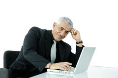 Businessman working on laptop. Mature businessman working on laptop computer at office desk, smiling, isolated on white background Stock Photography