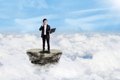 Businessman working with laptop above clouds Royalty Free Stock Photography