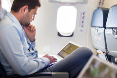 Businessman working with laptop on airplane. Casually dressed middle aged man working on laptop in aircraft cabin during his business travel. Shallow depth of Stock Image