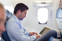 Businessman working with laptop on airplane. Casually dressed middle aged man working on laptop in aircraft cabin during his business travel. Shallow depth of Stock Photography