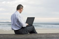 Businessman working with laptop on a beach Stock Photos