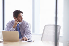 Businessman Working On Laptop At Boardroom Table Stock Photo