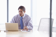 Businessman Working On Laptop At Boardroom Table Stock Photography