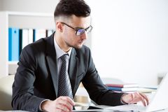 Businessman working with laptop. In an office Stock Photos