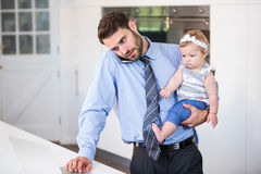 Businessman working on laptop while carrying daughter Royalty Free Stock Photo