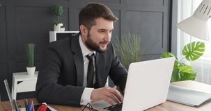 Businessman working on laptop and celebrating stock footage