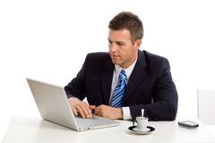 Businessman working on laptop computer. Sitting at desk and looking seriously at screen Stock Photos