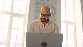 The bearded man with glasses in white using laptop indoors. Businessman working on laptop computer. Businessman working on laptop computer. the bearded man with stock footage