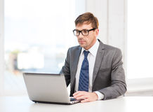 Businessman working with laptop computer. Technology, business and office concept - handsome businessman working with laptop computer Royalty Free Stock Images