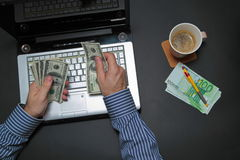 Businessman working on laptop and counting money. While as he drinks coffee Stock Photography