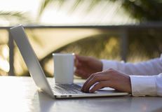 Businessman working with laptop and cup of coffee at sunrise. Close up Royalty Free Stock Images