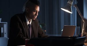 Businessman working on laptop in dark office. African american businessman working on laptop late in dark office stock footage