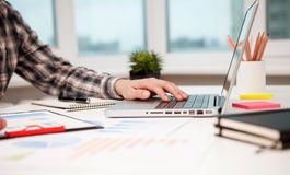 Businessman working laptop at the desk in modern office. Screening potential business deals by analyzing market strategies, resume reviewing, organized royalty free stock images