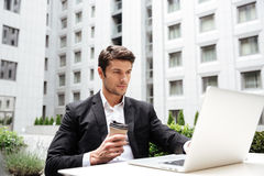 Businessman working with laptop and drinking coffee outdoors Royalty Free Stock Image