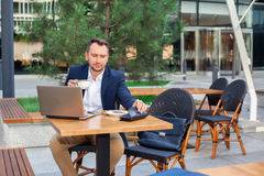 Businessman working on laptop, drinking coffee. Businessman working on laptop, sitting at a table on the street in a cafe, drinking coffee Royalty Free Stock Images