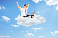 Businessman working on laptop and gesturing happiness seated on. Young businessman working on a laptop and gesturing happiness seated on cloud with blue sky in Royalty Free Stock Image