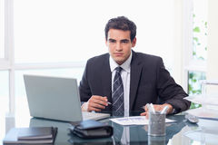 Businessman working with a laptop and a graph Royalty Free Stock Images