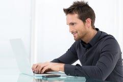 Businessman Working On Laptop. Happy Businessman Working On Laptop In Office Stock Photo